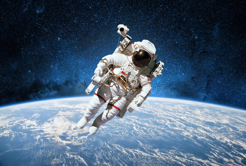 Astronaut in outer space with planet earth as backdrop. Elements royalty free stock images