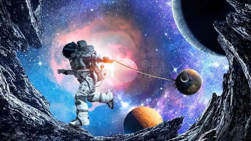 Fantasy image with spaceman catch planet. Mixed media. Astronaut in outer space pulling planet on rope. Elements of this image are furnished by NASA vector illustration