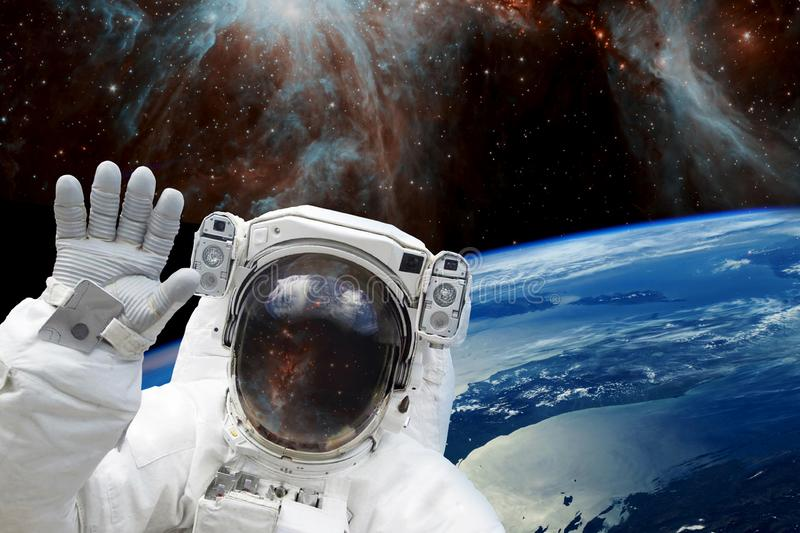 Astronaut in outer space in spacesuit against of the earth`s blue orbit and space. elements of this image furnished by NASA royalty free stock photography