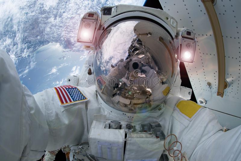 The astronaut in a space suit, does selfie, in an outer space, at the space station. Elements of this image were furnished by NASA. For any purpose stock photo