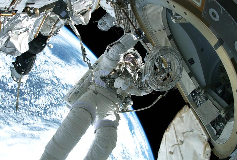 The astronaut in a space suit, in an outer space, is engaged in repair of station. Elements of this image were furnished by NASA stock photos