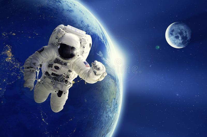 Astronaut or Spaceman floating in space with Earth planet and moon background royalty free stock photo