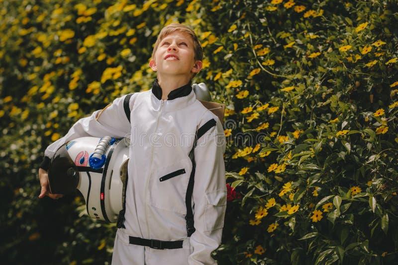 Astronauta del muchacho que se coloca al aire libre y que mira para arriba foto de archivo