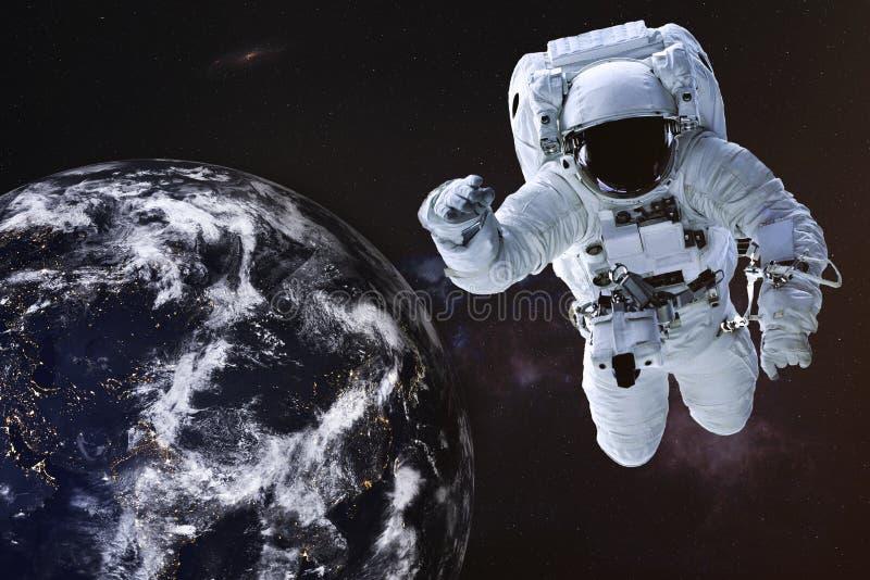 Astronauta en espacio exterior cerca de la tierra de la noche imagen de archivo libre de regalías