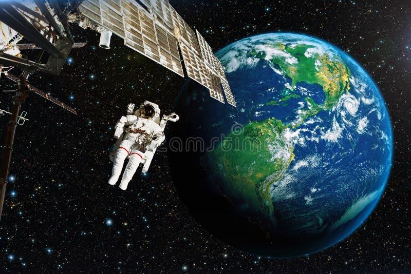 Astronauta en espacio exterior contra el contexto del eart del planeta fotos de archivo