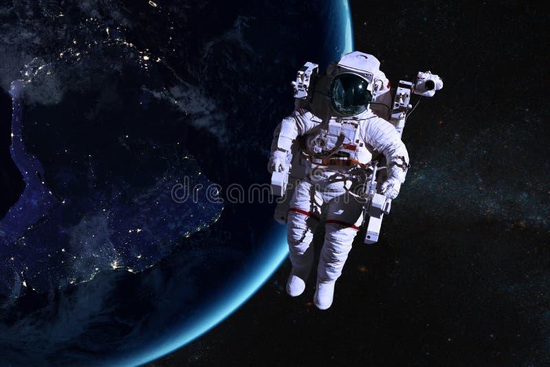 Astronauta en espacio exterior en el fondo de la tierra de la noche imagenes de archivo