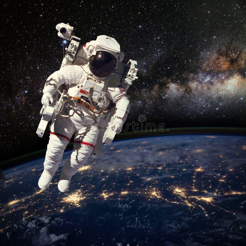 Astronauta en espacio exterior sobre la tierra durante noche elem fotos de archivo libres de regalías