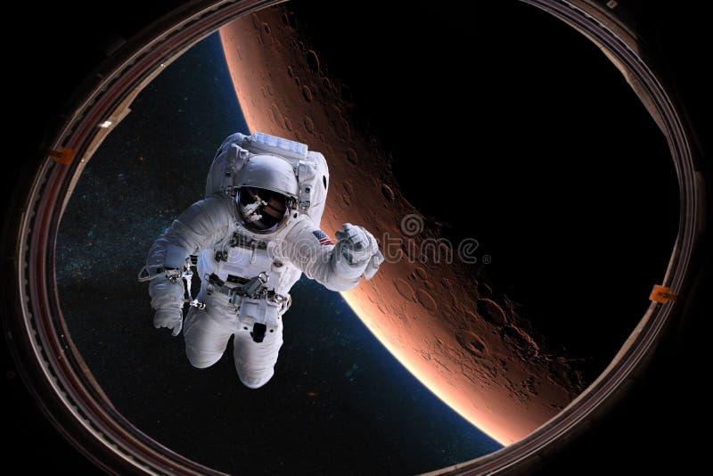 Astronauta nello spazio cosmico dall'oblò su fondo del Marte Elementi di questa immagine ammobiliati dalla NASA fotografia stock libera da diritti