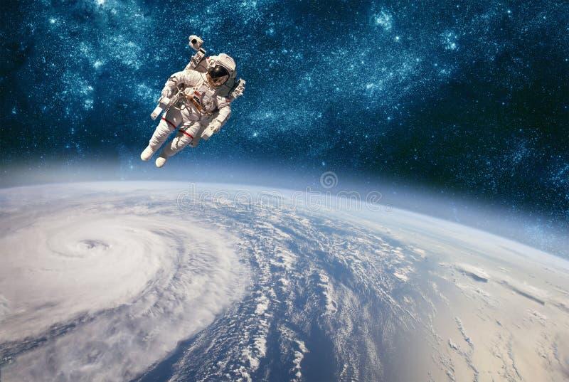 Astronauta no espaço contra o contexto da terra do planeta Tufão sobre a terra do planeta fotos de stock royalty free
