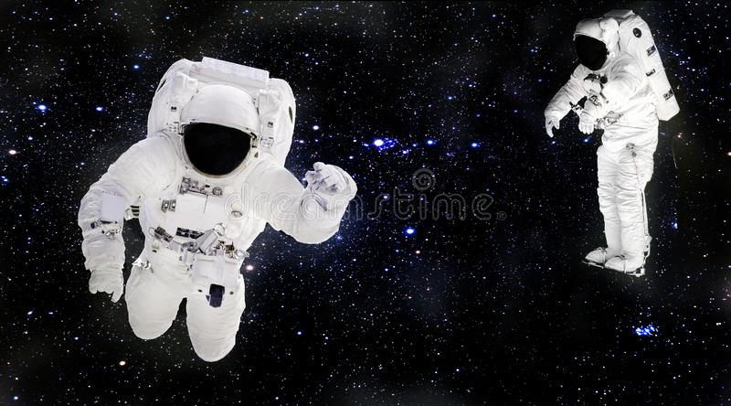 Astronautas en los spacesuits que flotan en espacio exterior Spacemans en el trabajo foto de archivo libre de regalías