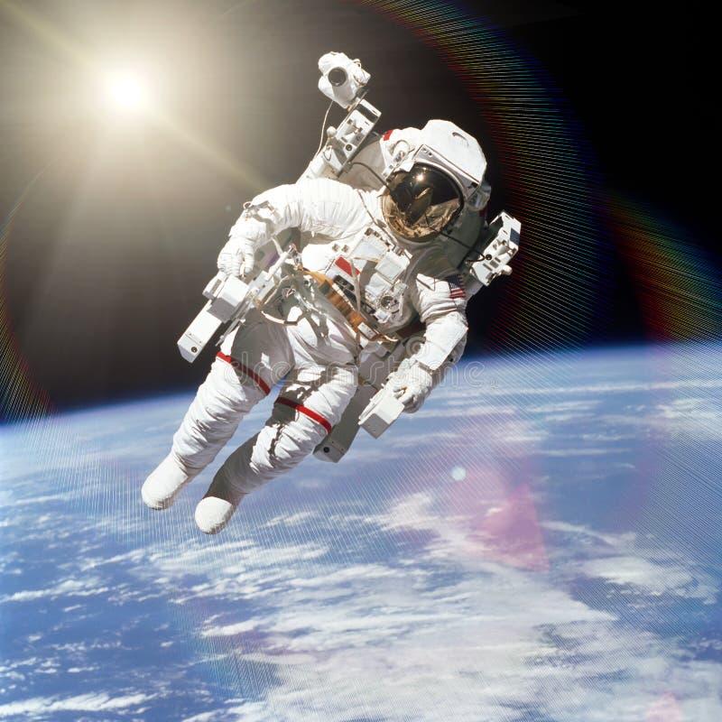 Astronaute dans l'espace extra-atmosphérique sur le fond de la terre image libre de droits