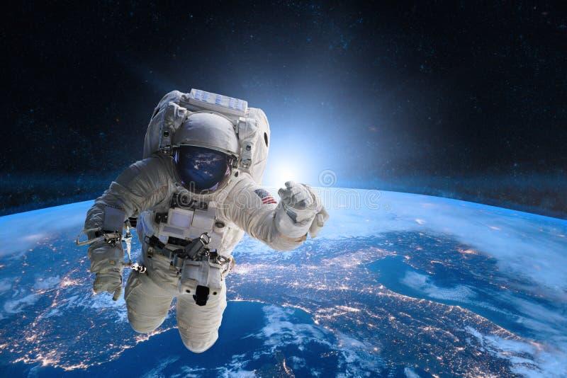 Astronaute dans l'espace extra-atmosphérique sur le fond de la terre image stock