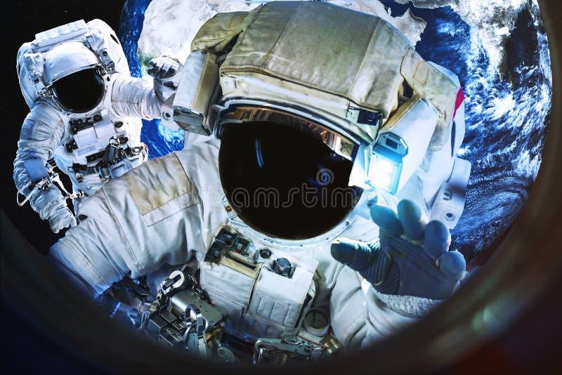 Astronauten dichtbij de Aardeplaneet in illuminator van ruimteschip stock fotografie