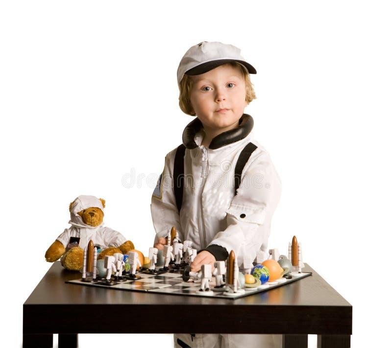 Astronautenjunge, der Schach spielt stockbild