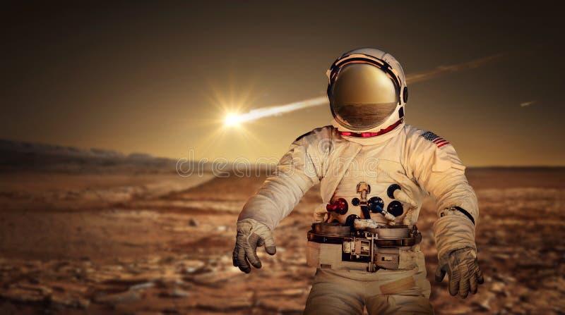Astronautet som undersöker yttersidan av den röda planeten, fördärvar royaltyfri bild