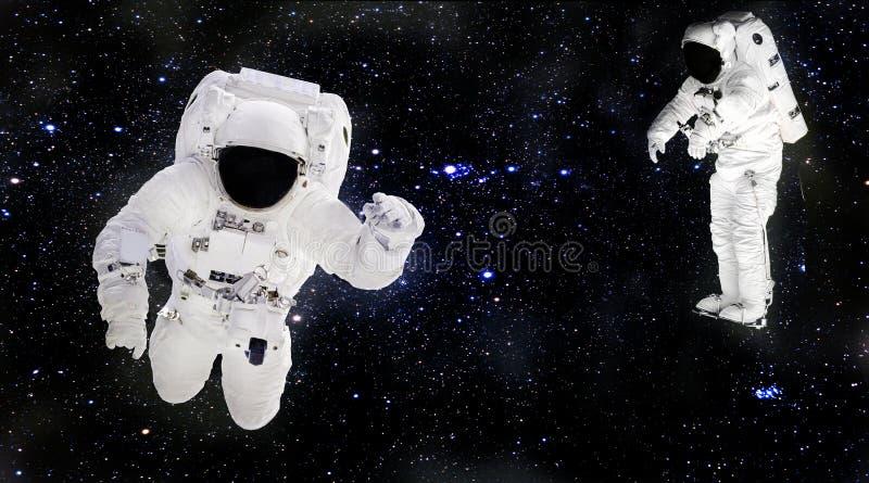 Astronauti in tute spaziali che galleggiano nello spazio cosmico Spacemans sul lavoro fotografia stock libera da diritti