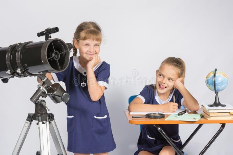 Astronomen för flickan ser hemskt in i avståndet, en klasskompis med ett leende som ses henne arkivbilder