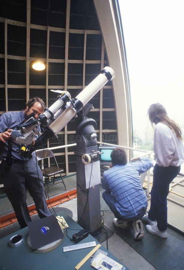 Astronomi che per mezzo di un telescopio fotografia stock