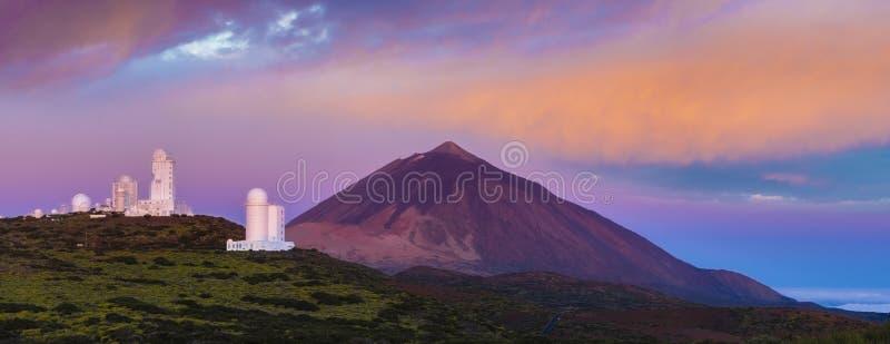 Astronomisch waarnemingscentrum tegen de achtergrond van een vulkaan bij stock afbeelding
