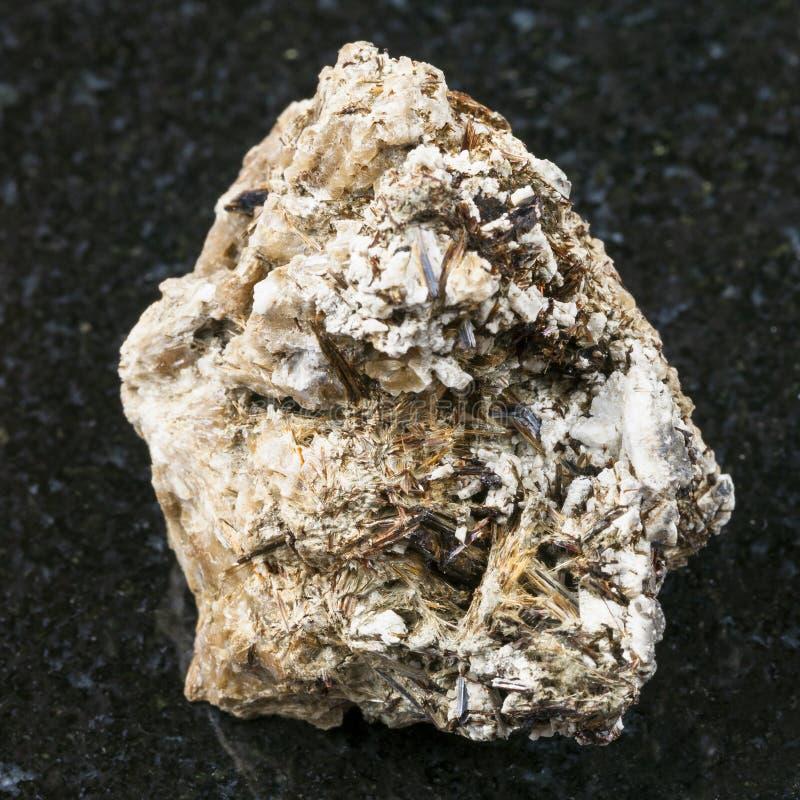 Astrophyllite kristaller i grova Natrolite på mörker arkivfoto