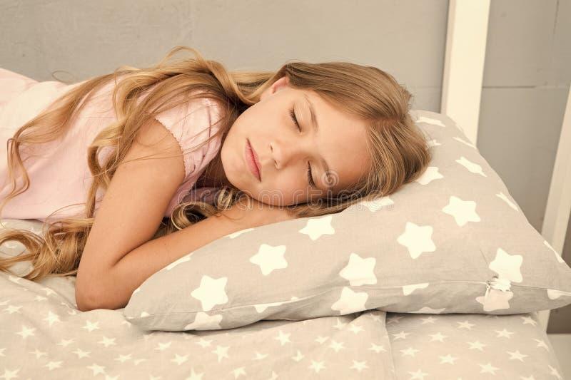 Astuces saines de sommeil Sommeil de fille sur le petit fond de literie d'oreiller Les longs cheveux boucl?s d'enfant tombent fin photos libres de droits