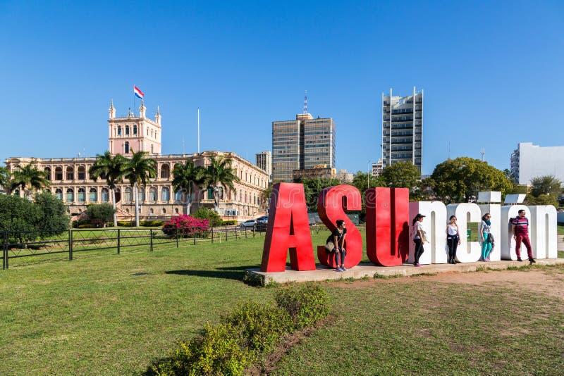 ASUNCION, PARAGUAY - 13 de julio de 2018: Cinco turistas están presentando con las letras de ASUncion y el palacio presidencial e foto de archivo libre de regalías