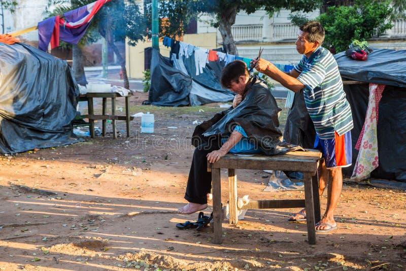 Outdoor haircut in slums of Asuncion city. Hairdressing on streets of Ciudad de Asunción Paraguay. Two men, tent camp. ASUNCION, PARAGUAY - July 13, 2018 stock images