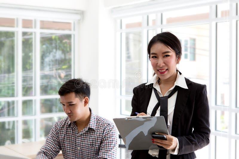 Asunto asiático joven Hombre de negocios feliz con un ordenador portátil en una mesa en la oficina fotos de archivo