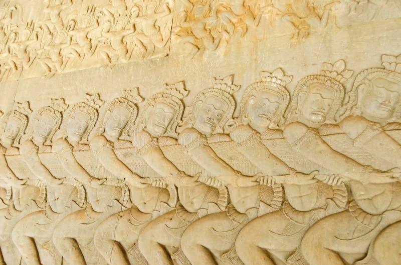 Asuras utilisant le serpent Vasuki pour battre la mer sur le bas-relief du barattage de la mer du lait dans Angkor Vat photos stock