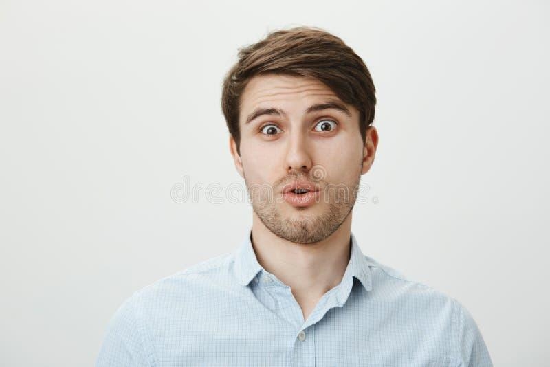 Asustan y se aturden al individuo de ver alguien muy feo Retrato de la cabeza inclinable chocada y confundida del hombre hermoso foto de archivo