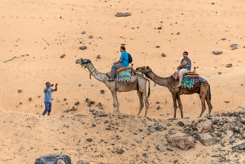 ASWAN,EGYPT 18.05.2018 Tourists aboard camel tour to Nubian village the west bank of the River Nile in the Aswan region stock photos