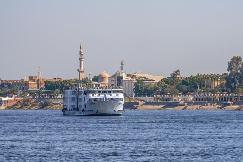 12 11 2018 Aswan, Egypte die, een reusachtige cruiseveerboot zich langs een Nijl tegen de achtergrond van een stad bewegen stock foto