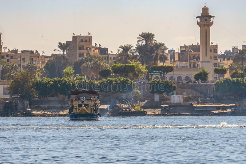 12 11 2018 Aswan, Egypten, en enorm kryssningfärja som fortskrider en nile mot bakgrunden av en stad royaltyfri foto