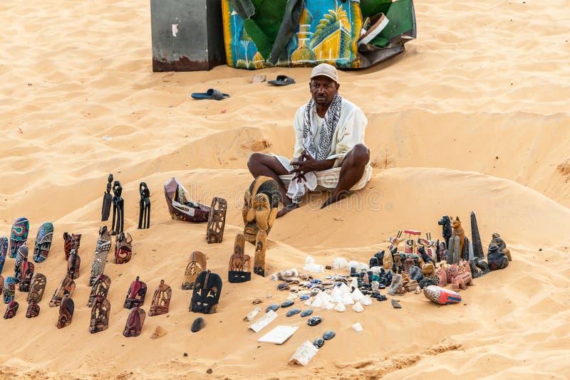 ASWAN EGYPTEN 20 05 Souvenirsäljare för 18 män med rullningslagret på fjärdsanden nära Assuan i Egypten royaltyfri foto