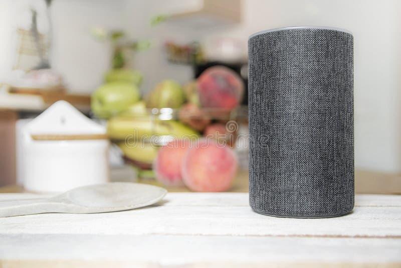 Asystent osobisty łączył głośnika na drewnianym stole w Mądrze domu w kuchni Następnie, niektóre naczynia, jedzenie i owoc, zdjęcia royalty free