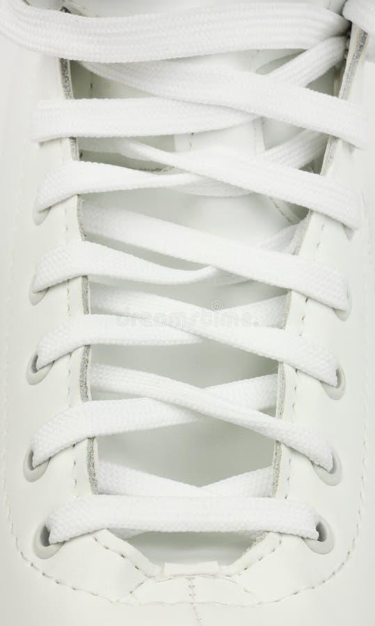 Ató cuidadosamente la bota de cuero blanca de los patines, cordones de la materia textil, primer fotos de archivo