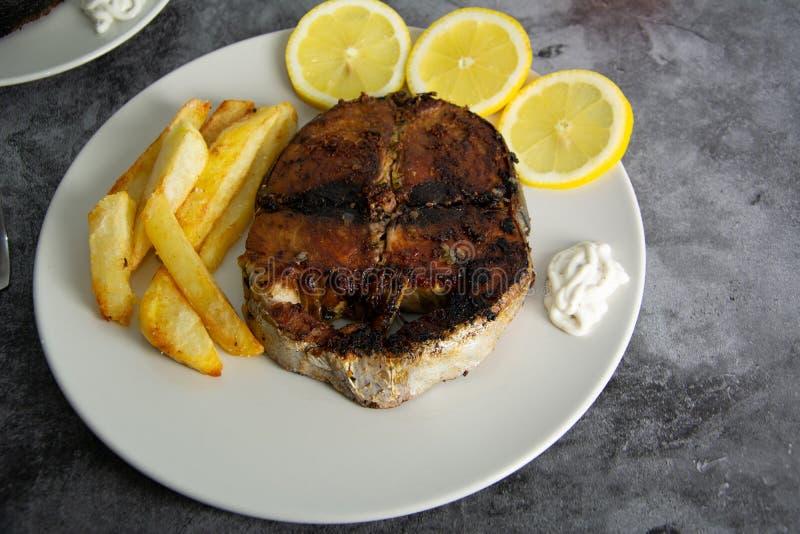 Atún asado a la parrilla sazonado con el limón, el ajo y patatas Alimento sano imagen de archivo libre de regalías