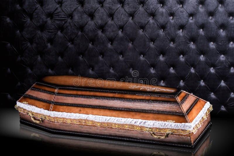 Ataúd marrón de madera cerrado con el paño en fondo de lujo gris ataúd con la sombra en fondo fotos de archivo