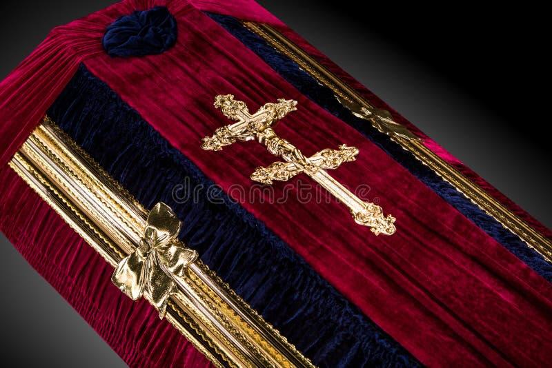 Ataúd rojo cerrado del terciopelo cubierto con el paño aislado en fondo gris primer del ataúd con la cruz de la iglesia del oro fotografía de archivo