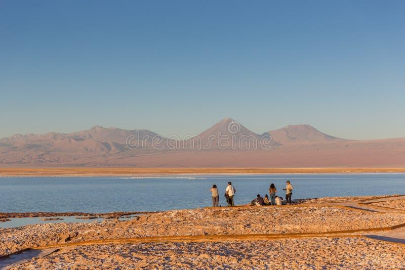 Atacama, Chile - 9 de octubre de 2017 - grupo de turistas que aprecian la puesta del sol en la sal plana, agua azul, volcán del d fotos de archivo