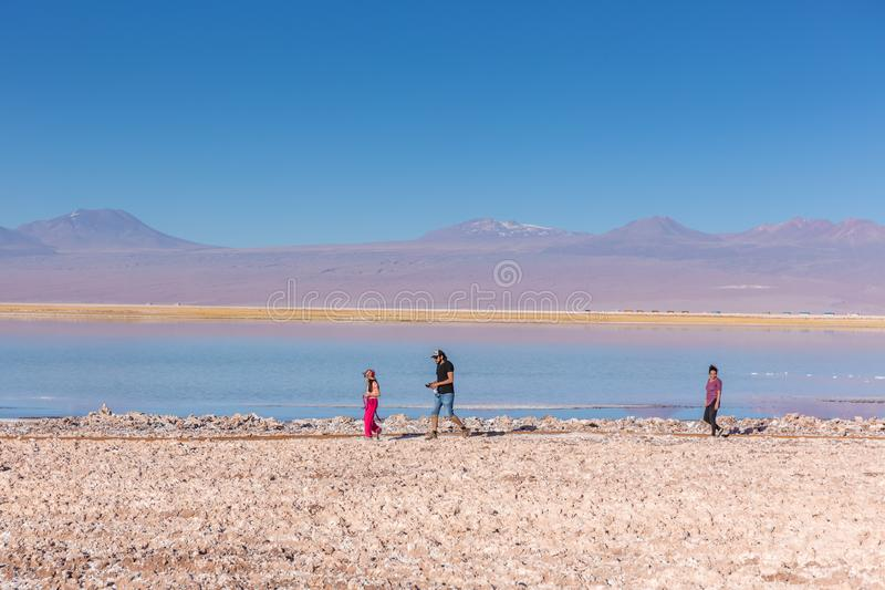 Atacama, Chile - Oct 9th 2017 - Narrow angle shot of parent and a child walking around of the Atacama salar in a fade light , afte. Rnoon, volcano in the stock photo