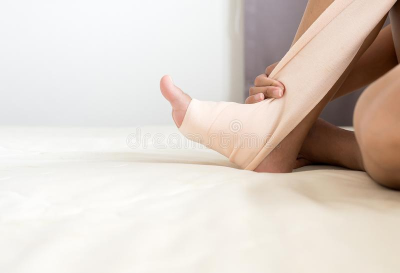 Atadura de colocação fêmea em seu tornozelo ferido, mulher que usa a atadura elástica com pé fotografia de stock royalty free