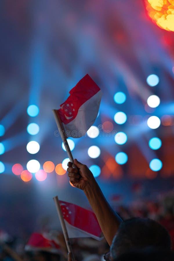 Ataque à mão com uma bandeira de singapore durante o 54.º desfile nacional de Singapura em 9 de agosto de 2019 imagens de stock royalty free