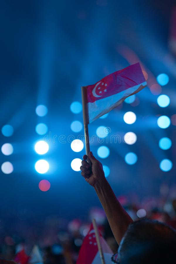 Ataque à mão com uma bandeira de singapore durante o 54.º desfile nacional de Singapura em 9 de agosto de 2019 imagem de stock royalty free