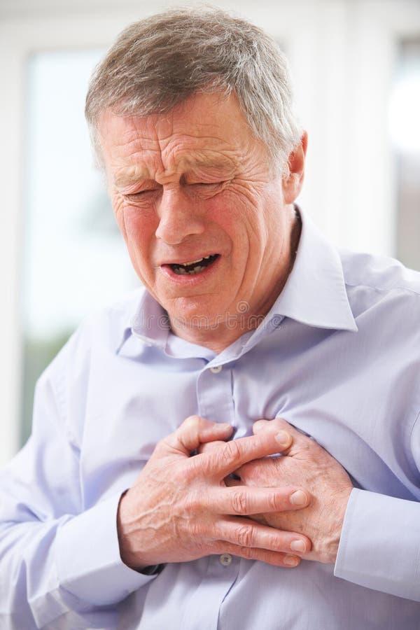 Ataque del corazón sufridor al hombre mayor en casa foto de archivo