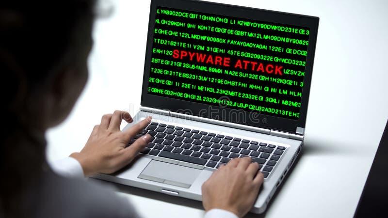 Ataque del Spyware en el ordenador portátil, mujer que elabora en la oficina, ciberdelincuencia, cierre imagenes de archivo