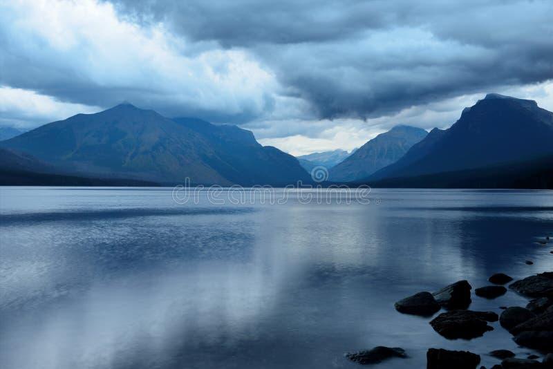Ataque nas montanhas no lago McDonald no parque nacional de geleira após o por do sol fotos de stock