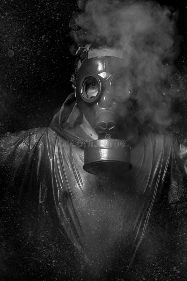 Ataque nuclear. Un hombre en una careta antigás en el humo. backg artístico imagen de archivo