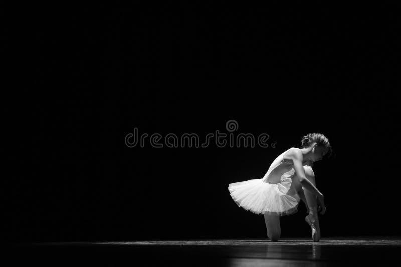 Atar los zapatos de ballet antes de realizar imagen de archivo libre de regalías