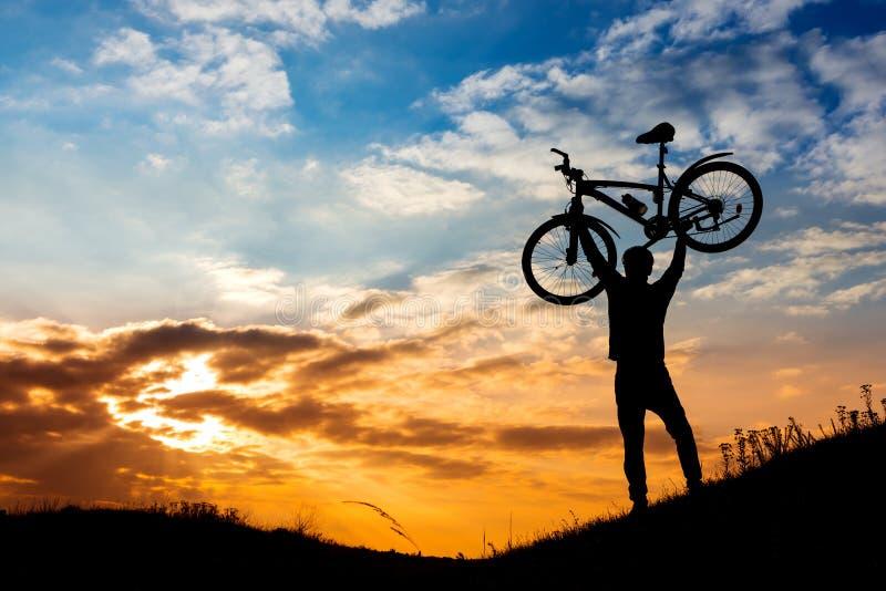 Atardecer en las montañas con el placer del ganador del ciclismo de montaña imagen de archivo
